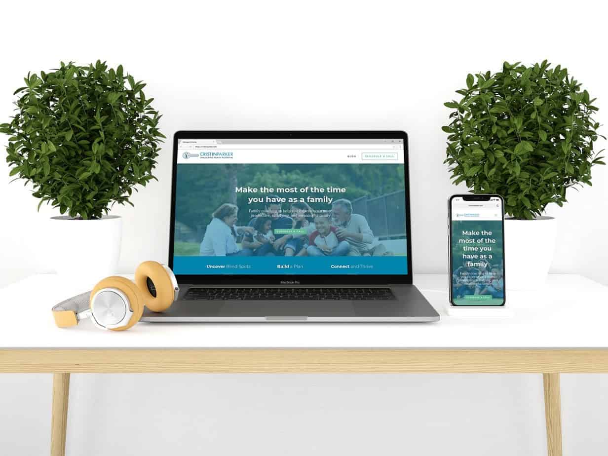 laptop and phone on desk with plants